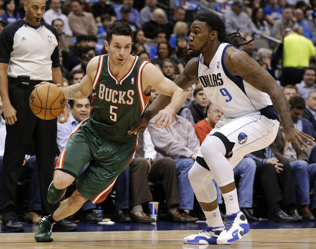 Milwaukee Bucks' J.J. Redick (5) attempts to get past Dallas Mavericks' Jae Crowder (9) on a drive to the basket in the first half of an NBA basketball game Tuesday, Feb. 26, 2013, in Dallas. (AP Photo/Tony Gutierrez)