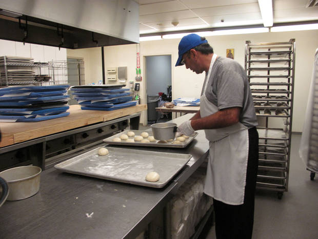 Volunteer Mike Sleem places unbaked rolls on a baking sheet bound for the oven at St. Elijah Antiochian Orthodox Christian Church. The rolls will be sold at the church's annual food festival and holiday bake sale Friday and Saturday at 15000 N May. Photo by Carla Hinton, The Oklahoman <strong></strong>