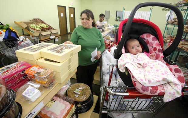 Delia Gramajo, Okla. City, selects from the baked goods while her daughter Joyce, 4 months old, rests in the shopping cart at the Urban Mission Food Resource Center, 3737 N Portland in Oklahoma City Thursday, July 12, 2012. Photo by Paul B. Southerland, The Oklahoman