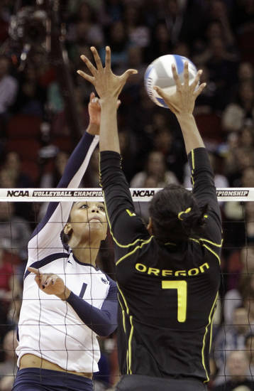Penn State's Ariel Scott (1) spikes the ball through the block attempt by Oregon's Ariana Williams (7) during the national semifinals of the NCAA college women's volleyball tournament semifinal in Louisville, Ky., Thursday, Dec. 13, 2012.  (AP Photo/Garry Jones)