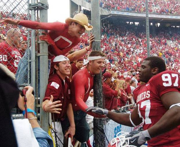 OU fans reach out to celebrate OU's 12-0 win over Texas with Cory Bennett (97) Saturday, October 9, 2004, in Dallas.