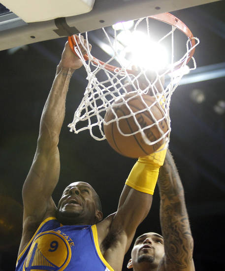 Golden State Warriors guard Andre Iguodala, left, dunks the ball with Los Angeles Lakers center Robert Sacre, right, defending in the second quarter during an NBA basketball preseason game Saturday, Oct. 5, 2013, in Ontario, Calif.  (AP Photo/Alex Gallardo)