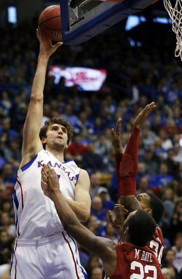 Kansas center Jeff Withey, left, shoots over Oklahoma defenders, including forward Amath M'Baye (22), during the first half of an NCAA college basketball game in Lawrence, Kan., Saturday, Jan. 26, 2013. (AP Photo/Orlin Wagner)