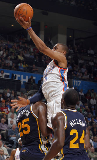 Oklahoma City's Russell Westbrook shoots in between Utah's Al Jefferson (25) and Paul Millsap (24) during the NBA basketball game between the Oklahoma City Thunder and Utah Jazz in the Oklahoma City Arena on Sunday, Oct. 31, 2010. Photo by Sarah Phipps, The Oklahoman