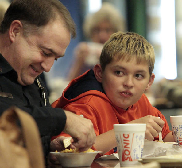 Greg Roberts and son Drew, 10, dine together Thursday at the annual Police-Fire Chili Supper that raises money for the Cleveland County Christmas Store. PHOTO BY STEVE SISNEY, THE OKLAHOMAN <strong>STEVE SISNEY</strong>