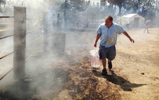 A resident carries a bucket of water to help fight the brush fire burning right up to his property in the hills above Banning, Calif., on Wednesday, May 1, 2013. (AP Photo/The Press-Enterprise, Terry Pierson)