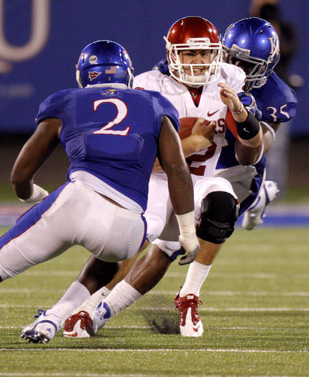 Oklahoma's Landry Jones (12) is brought down between Kansas' Darius Willis (2) and Toben Opurum (35) during the college football game between the University of Oklahoma Sooners (OU) and the University of Kansas Jayhawks (KU) at Memorial Stadium in Lawrence, Kansas, Saturday, Oct. 15, 2011. Photo by Bryan Terry, The Oklahoman