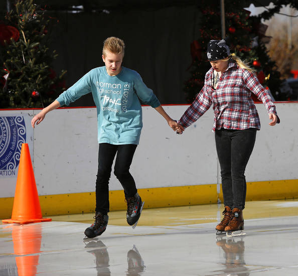 Austin Pruett and his mother, Melissa Kissner, circle the rink at the Norman Outdoor Holiday Ice Rink at Interstate 35 and Lindsey Street in Norman.  PHOTO BY JIM BECKEL, THE OKLAHOMAN
