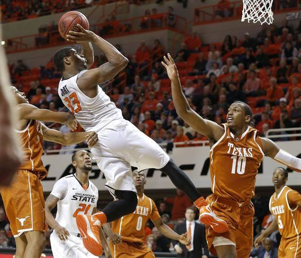 Oklahoma State's Marcus Smart (33) goes to the basket between Texas' Jonathan Holmes (10) and Demarcus Holland during an NCAA college basketball game between the Oklahoma State Cowboys (OSU) and the University of Texas Longhorns at Gallagher-Iba Arena in Stillwater, Okla., Wednesday, Jan. 8, 2014. Oklahoma State won 87-74. Photo by Bryan Terry, The Oklahoman