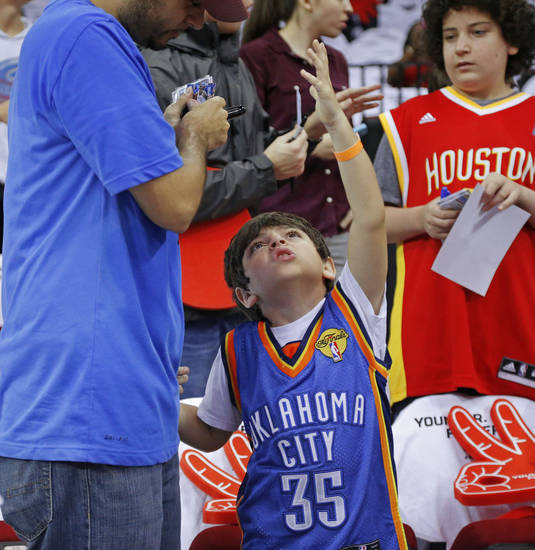 Michael Montes, 8, of Houston, talks with his father, Mike Montes before Game 3 in the first round of the NBA playoffs between the Oklahoma City Thunder and the Houston Rockets at the Toyota Center in Houston, Texas, Sat., April 27, 2013. Photo by Bryan Terry, The Oklahoman