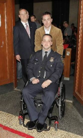Oklahoma police officer Chad Peery, in a wheelchair being pushed by his brother Mark Peery, leaving the courtroom after the sentencing of Cadmio Lopez at the Oklahoma County Courthouse in Oklahoma City Friday, Jan. 27, 2012. Photo by Paul B. Southerland