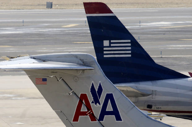 American Airlines and US Airways jets prepare for flight at gate at the Philadelphia International Airport, Thursday, Feb. 14, 2013, in Philadelphia. The merger of US Airways and American Airlines has given birth to a mega airline with more passengers than any other in the world. (AP Photo/Matt Rourke)
