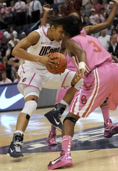 Connecticut's Maya Moore goes head-to-head with Oklahoma's Aaryn Ellenberg (3) in the first half of an NCAA college basketball game in Hartford, Conn., Monday, Feb. 14, 2011. (AP Photo/Bob Child)