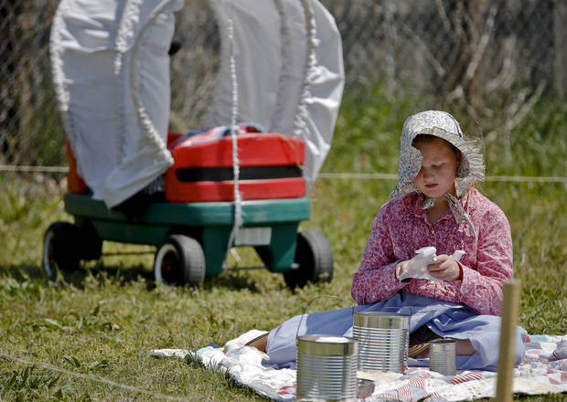 Jessee Pearce grabs a bite to eat next to her covered wagon during the Oklahoma Land Run celebration at Mustang Trails Elementary on Monday, April 22, 2013, in Mustang, Okla.   Photo by Chris Landsberger, The Oklahoman