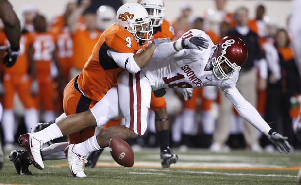 OSU's Patrick Levine knocks the ball loose from OU's Jermaine Gresham during the first half of the college football game between the University of Oklahoma Sooners (OU) and Oklahoma State University Cowboys (OSU) at Boone Pickens Stadium on Saturday, Nov. 29, 2008, in Stillwater, Okla. STAFF PHOTO BY BRYAN TERRY
