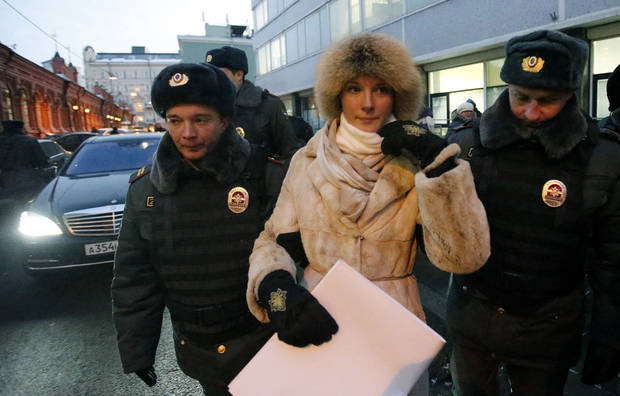 Police officers detain a protester near the State Duma, in Moscow, Russia, Wednesday, Dec. 19, 2012. People picketed parliament's lower chamber, which is set to debate an amendment that would ban Americans from adopting Russian children. (AP Photo/Misha Japaridze)