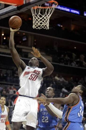 Charlotte Bobcats center Emeka Okafor (50) scores as the Oklahoma City Thunder's  Jeff  Green (22) and Desmond Mason (34) in an NBA basketball game in Charlotte, N.C. on Wednesday, Dec. 3, 2008. Charlotte won 103-97. AP Photo/Nell Redmond
