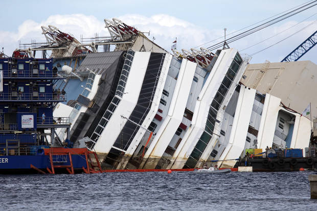 The Costa Concordia ship lies on its side on the Tuscan Island of Giglio, Italy, Monday, Sept. 16, 2013. An international team of engineers is trying a never-before attempted strategy to set upright the luxury liner, which capsized after striking a reef in 2012 killing 32 people. (AP Photo/Andrew Medichini)