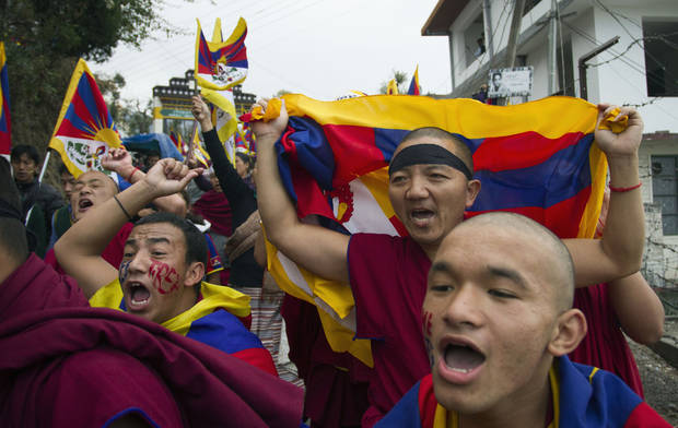 Exiled Tibetan Buddhist monks carrying Tibetan flags shout slogans during a protest march in Dharmsala, India, as they mark the anniversary of a failed 1959 uprising against Chinese rule, Sunday, March 10, 2013. Police in India prevented a Tibetan man from setting himself on fire as hundreds of Tibetan exiles gathered to mark the anniversary in Dharmsala, the home of Tibet's government in exile. (AP Photo/ Ashwini Bhatia)