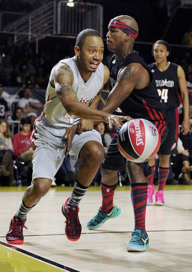 Terrence Jenkins, left, drives the ball past Ne-Yo in the second half of the NBA All-Star celebrity basketball game Friday, Feb. 15, 2013, in Houston. (AP Photo/Pat Sullivan)