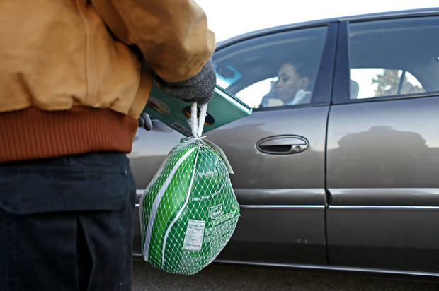 A car drives up as a Feed The Children volunteer holds a frozen turkey as part of a distribution to families. Photo by Bryan Terry, The Oklahoman <strong>BRYAN TERRY - THE OKLAHOMAN</strong>