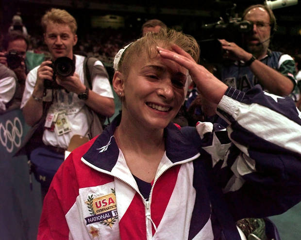 Members of the media pursue USA's Shannon Miller, of Edmond, Ohio, after the US women's national gymnastics team won the gold in the team competition at the 1996 Centennial Summer Olympics Games in Atlanta on Tuesday, July 23, 1996.  (AP Photo/Amy Sancetta)