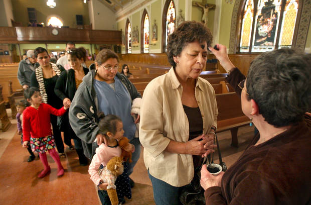 Cristina Parsons, right, applies ashes to the forehead of Frances Encinas at the end of Ash Wednesday mass at St. John's Cathedral in downtown Fresno, Calif. Wednesday, Feb. 22, 2012. (AP Photo/The Fresno Bee, Mark Crosse)