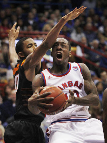 Kansas guard Tyshawn Taylor (10) drives past Oklahoma State forward Michael Cobbins (20) for a basket during the first half of an NCAA college basketball game in Lawrence, Kan., Saturday, Feb. 11, 2012. (AP Photo/Orlin Wagner) <strong>Orlin Wagner</strong>