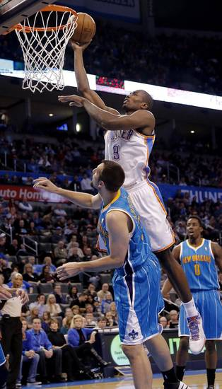 Oklahoma City Thunder's Serge Ibaka (9) lays in a shot over New Orleans Hornets' Ryan Anderson (33) during the NBA basketball game between the Oklahoma City Thunder and the New Orleans Hornets at the Chesapeake Energy Arena on Wednesday, Feb. 27, 2013, in Oklahoma City, Okla. Photo by Chris Landsberger, The Oklahoman
