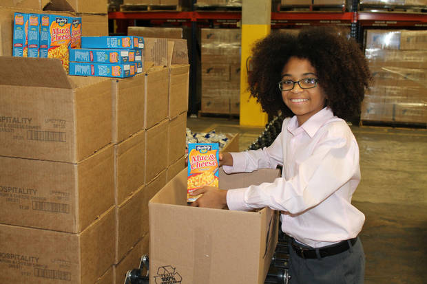 Joshua Williams, 12, of Miami, Fla., who founded his own charity at age 5, checks out the packed boxes of food at one of Feed the Children's distribution warehouses that he toured during a recent visit to Oklahoma City. PHOTO PROVIDED. <strong></strong>