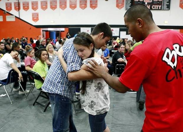 Freshman Angela Vargas gets a hug from student Kasra Kaidan (left) and Challenge Week staff member Romeo Marquez after Angela spoke to students during Challenge Day at Putnam City High School in Oklahoma City on Wednesday, September 21, 2011. Challenge Day is a group building exercise to end bullying and other discipline issues. Photo by John Clanton, The Oklahoman ORG XMIT: KOD