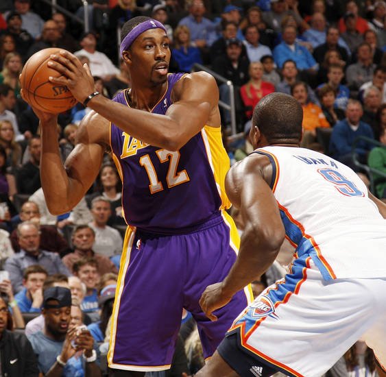 Los Angeles' Dwight Howard (12) looks to pass around Oklahoma City's Serge Ibaka (9) during an NBA basketball game between the Oklahoma City Thunder and the Los Angeles Lakers at Chesapeake Energy Arena in Oklahoma City, Friday, Dec. 7, 2012. Oklahoma City won, 114-108. Photo by Nate Billings, The Oklahoman