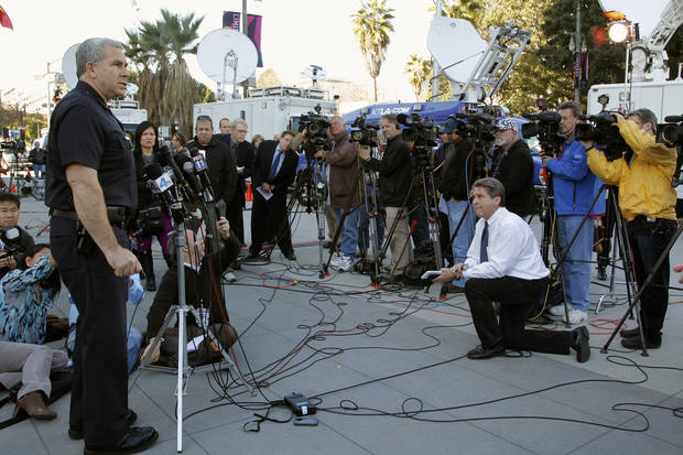 Los Angeles police Lt. Andrew Neiman, left, takes questions from the media at news conference about conviction of former police officer Christopher Jordan Dorner, outside the LAPD headquarters downtown Los Angeles Monday, Feb 11,  2013. Dorner was charged Monday with murdering a police officer and attempting to murder three others in Riverside County. (AP Photo/Nick Ut)