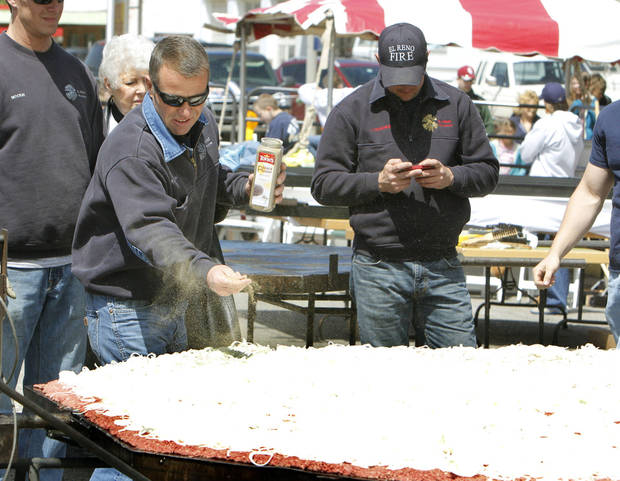 El Reno Fire Chief Kent Lagaly tosses pepper over a 750 lb. burger during the Fabulous Burger Day Festival in El Reno, OK, Saturday, May 4, 2013,  By Paul Hellstern, The Oklahoman
