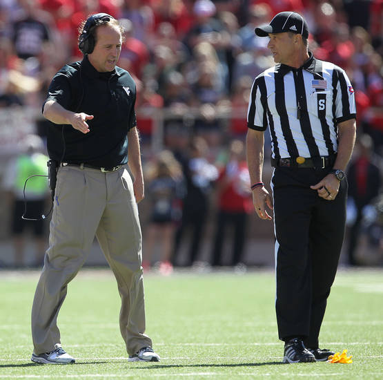 West Virginia head coach Dana Holgorsen has a discussion with sde judge Craig Falkner during during an NCAA college football game against Texas Tech in Lubbock, Texas, Saturday, Oct. 13, 2012. (AP Photo/Lubbock Avalanche-Journal, Stephen Spillman)