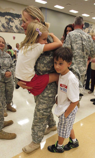 Staff Sgt. Sarah Scott, Noble, hugs her children Anna, 8, and Ethan, 9, as she and fellow soldiers from the 1-245th Airfield Operations Battalion return home on Tuesday, August 16, 2011, in Norman, Okla. after spending eight months in Afghanistan.