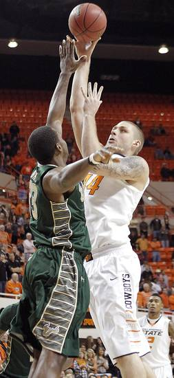 Oklahoma State 's Philip Jurick (44) shoots over South Florida Bulls' Kore White (33) during the college basketball game between Oklahoma State University (OSU) and the University of South Florida (USF) on Wednesday , Dec. 5, 2012, in Stillwater, Okla.   Photo by Chris Landsberger, The Oklahoman