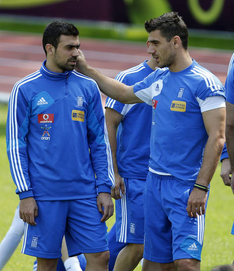 Greece's Costas Katsouranis, right, jokes with Yannis Maniatis during a training session at the Euro 2012 soccer championship in Legionowo about 25 kilometers (15 miles) north of Warsaw, Poland on Monday, June 18, 2012. (AP Photo/Thanassis Stavrakis)