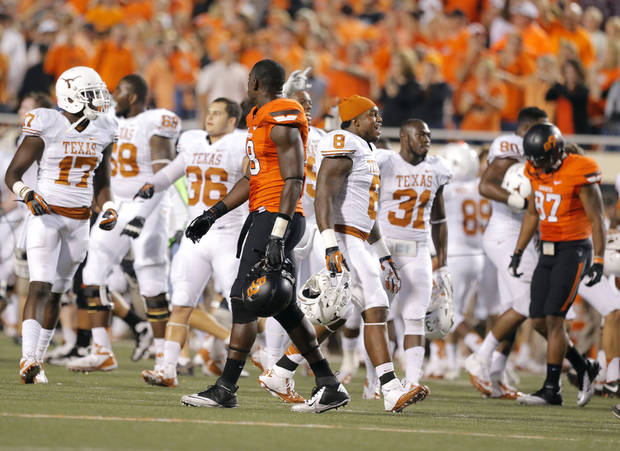 Oklahoma State's C.J. Curry (8) and Oklahoma State's Tracy Moore (87) walk off the field as Texas Celebrates following a college football game between Oklahoma State University (OSU) and the University of Texas (UT) at Boone Pickens Stadium in Stillwater, Okla., Saturday, Sept. 29, 2012. Texas on 41-36. Photo by Sarah Phipps, The Oklahoman