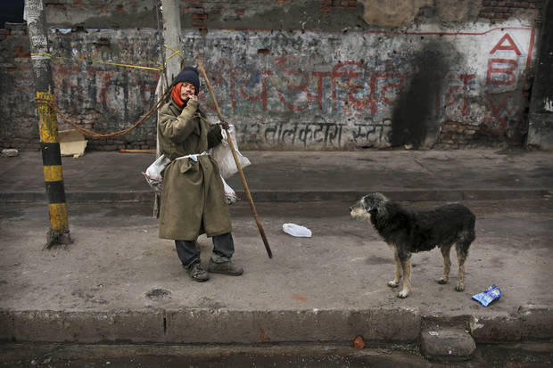 A stray dog watches an Indian man eating his breakfast in the street in New Delhi, India, Tuesday, Jan. 8, 2013. North India continues to face below average weather conditions with dense fog affecting flights and trains. More than 100 people have died of exposure as northern India deals with historically cold temperatures. (AP Photo/Kevin Frayer)
