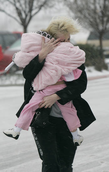 Julie Nelson shields her daughter Caiden Cauwell, 3, from the weather as she does some last-minute shopping in  Norman Thurs. Dec. 24, 2009. Photo by Jaconna Aguirre, The Oklahoman.