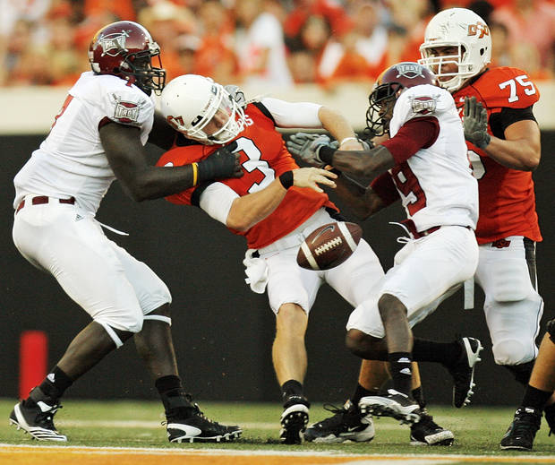 OSU quarterback Brandon Weeden (3) fumbles the football between Mario Addison (7), left, and Jimmie Anderson (19) of Troy as OSU's Nick Martinez (75) looks on in the second quarter during the college football game between the Oklahoma State University Cowboys (OSU) and the Troy University Trojans at Boone Pickens Stadium in Stillwater, Okla., Saturday, Sept. 11, 2010. Troy recovered the fumble. Photo by Nate Billings, The Oklahoman