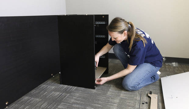 Mandi Hagler, city support analyst, puts her desk together in her office inside the new Edmond information technology building. PHOTO BY PAUL B. SOUTHERLAND, THE OKLAHOMAN. <strong>PAUL B. SOUTHERLAND - THE OKLAHOMAN</strong>