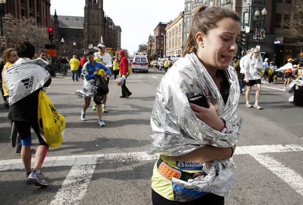 An unidentified Boston Marathon runner leaves the course crying near Copley Square following an explosion in Boston Monday, April 15, 2013. (AP Photo/Winslow Townson) ORG XMIT: MAWT101