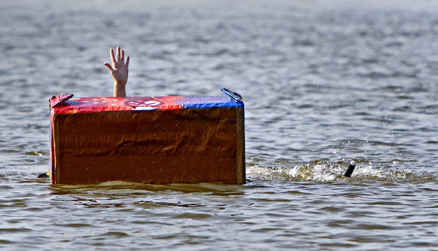 Monica Holmes, 15, reaches up as her boat sinks during Edmond&#039;s Cardboard Boat Regatta at Arcadia Lake in Edmond, Okla., Saturday, August 27, 2011. Photo by Bryan Terry, The Oklahoman