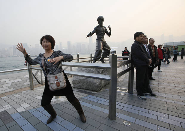 In this Jan. 11, 2013 photo, Mainland Chinese tourists pose in front of a bronze statue of the Hong Kong martial art actor Bruce Lee on the Avenue of Stars, the city&#039;s version of the Hollywood Walk of Fame in Hong Kong. He&#039;s arguably Hong Kong&#039;s most famous movie star but the city has done little to commemorate Bruce Lee, who shot to global stardom with films like &acirc;Enter the Dragon&acirc; but died in 1973 at age 32 of swelling of the brain. (AP Photo/Kin Cheung)