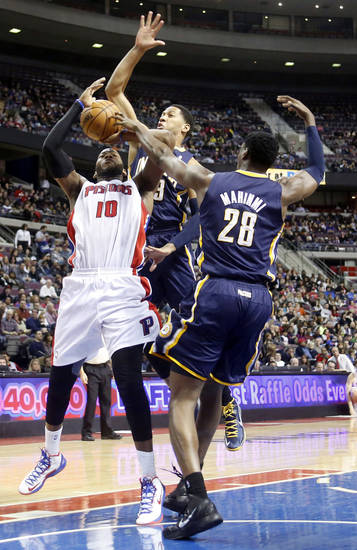 Detroit Pistons center Greg Monroe (10) is double-teamed while going to the basket against Indiana Pacers forward Danny Granger and center Ian Mahinmi (28) in the first half of an NBA basketball game Saturday, Feb. 23, 2013, in Auburn Hills, Mich. (AP Photo/Duane Burleson)