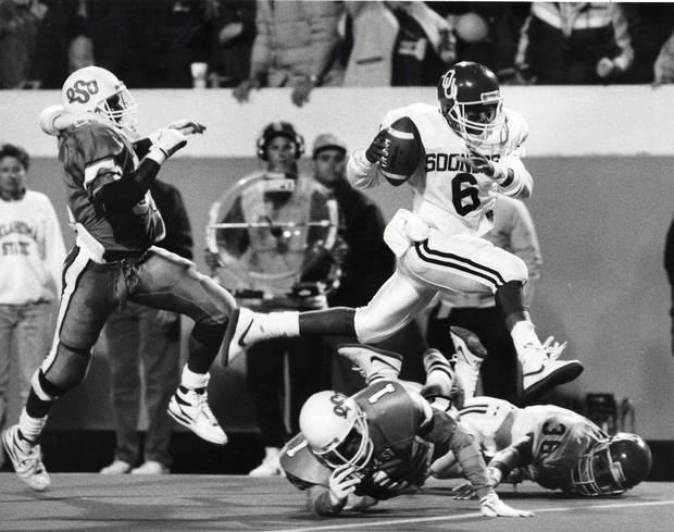 OU's Charles Thompson leaps over OSU's Mike Clark on his way to the winning touchdown in the fourth quarter of the Bedlam college football game on Nov. 5, 1988. Staff photo by David McDaniel