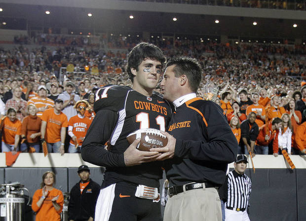OSU head coach Mike Gundy greets quarterback Zac Robinson (11) as 