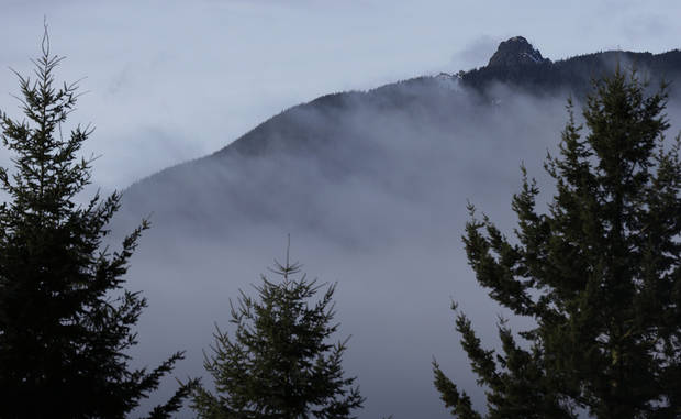 Rugged terrain surrounds the summit of Mount Si, upper right, Friday, Jan. 4, 2013, near North Bend, Wash. Searchers in the air and on the ground were looking for 29-year-old Kurt Ruppert of Lake City, Fla., who has been missing since a skydiving trip on Thursday. (AP Photo/Ted S. Warren)